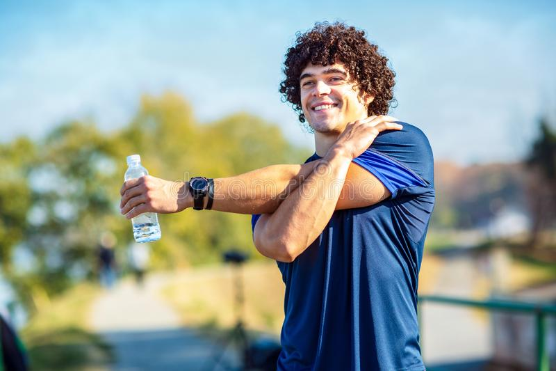 Hombre de la aptitud que estira al aire libre - aptitud, deporte, el entrenamiento y l imagen de archivo