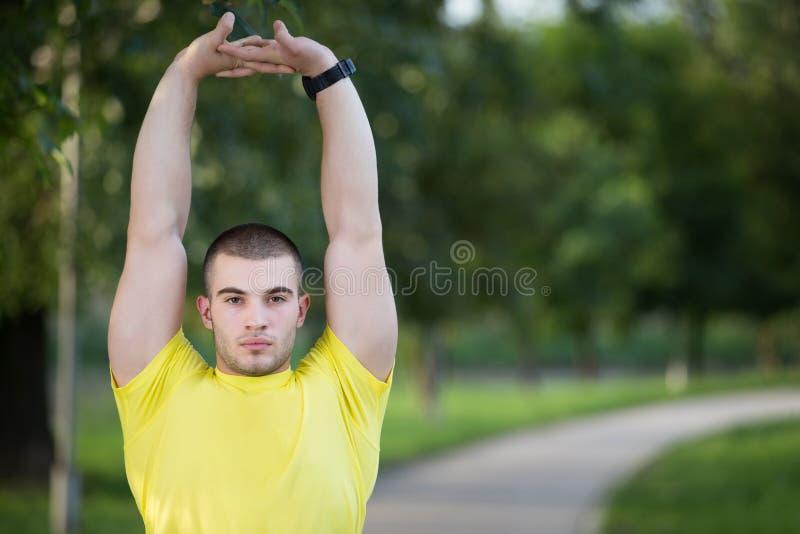 Hombre de la aptitud que estira el hombro del brazo antes de entrenamiento al aire libre Atleta de sexo masculino deportivo en un fotos de archivo