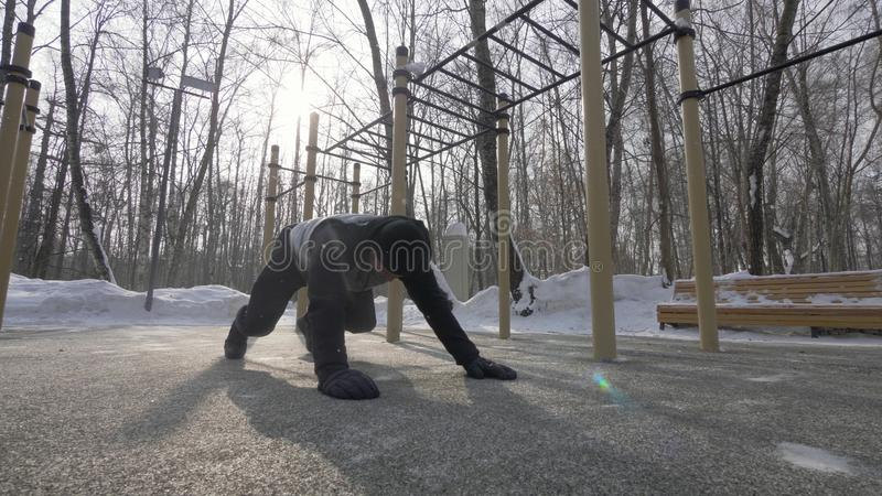 Hombre de la aptitud que hace pectorales y que estira ejercicios en el entrenamiento de los deportes de invierno imágenes de archivo libres de regalías