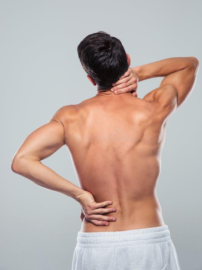 Hombre de la aptitud que se coloca con dolor de espalda imagen de archivo