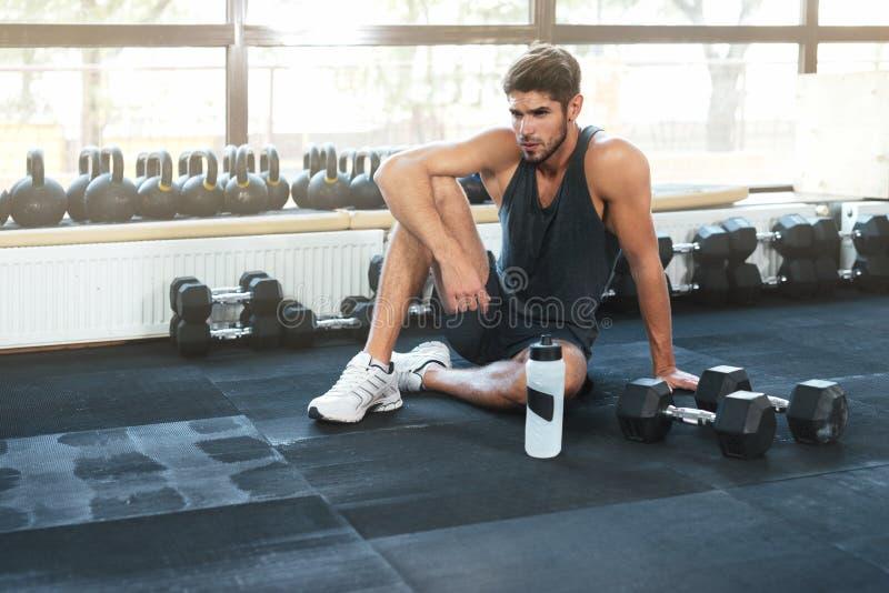 Hombre de la aptitud que se sienta en gimnasio imagen de archivo libre de regalías