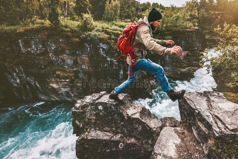 Hombre de la aventura que salta en rocas sobre el barranco del río foto de archivo libre de regalías