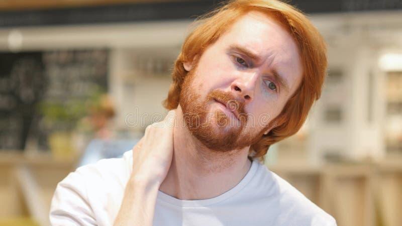 Hombre de la barba del pelirrojo con el dolor de cuello serio, interior imagenes de archivo