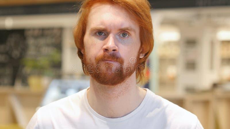 Hombre de la barba del pelirrojo que sacude la cabeza para rechazar la oferta, no fotografía de archivo libre de regalías