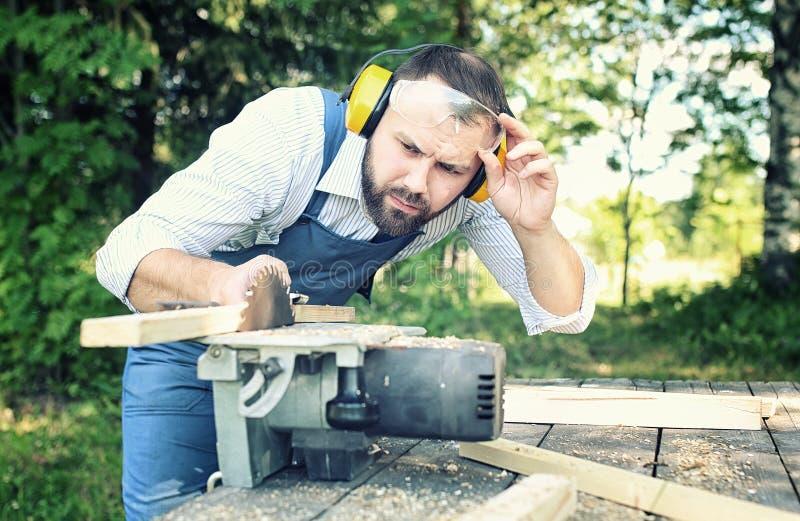 Hombre de la barba del trabajador con la sierra circular imágenes de archivo libres de regalías