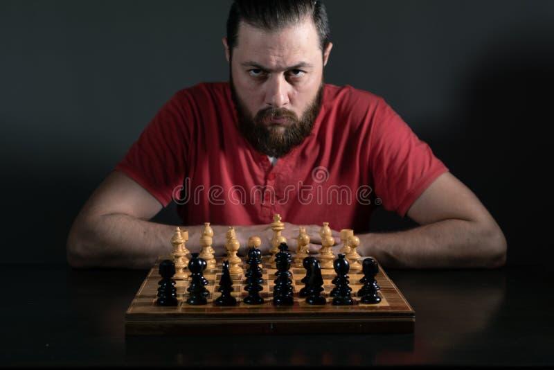 Hombre de la barba en la luz del estudio que mira enfocada la c?mara Tablero de ajedrez delante de ?l Toma de decisi?n del negoci imagen de archivo