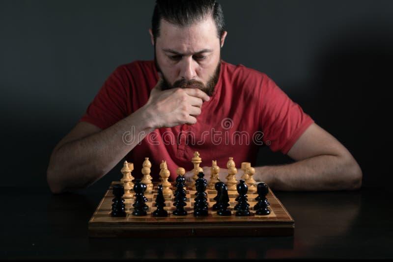Hombre de la barba en la luz del estudio que mira enfocada la c?mara Tablero de ajedrez delante de ?l Toma de decisi?n del negoci fotos de archivo