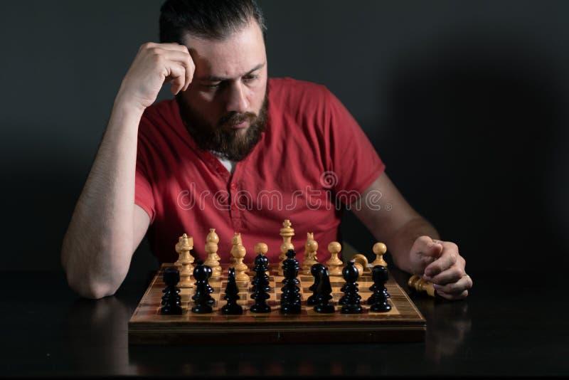 Hombre de la barba en la luz del estudio que mira enfocada la c?mara Tablero de ajedrez delante de ?l Toma de decisi?n del negoci foto de archivo