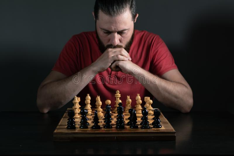 Hombre de la barba que piensa en qu? movimiento de ajedrez de realizarse Concepto de la toma de decisi?n del negocio imagen de archivo