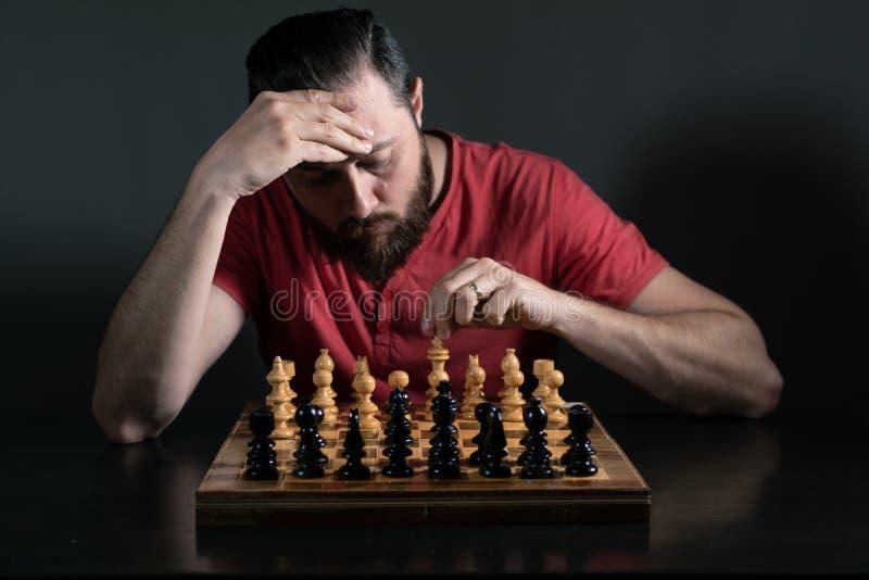 Hombre de la barba que toma la decisi?n dif?cil mientras que juega a ajedrez Toma de decisi?n del negocio fotografía de archivo