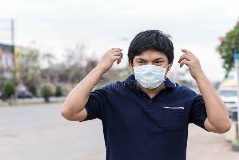 Hombre de la calle asiático que lleva máscaras protectoras , Hombre enfermo con la máscara que lleva de la gripe y nariz que sopl fotos de archivo libres de regalías