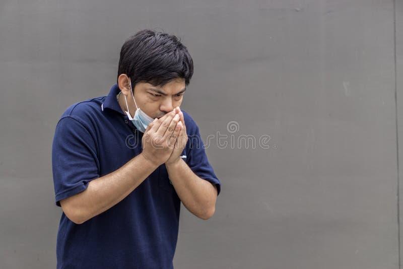 Hombre de la calle asiático que lleva máscaras protectoras , Hombre enfermo con la máscara que lleva de la gripe y nariz que sopl imagen de archivo libre de regalías