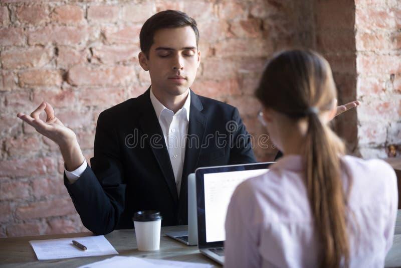 Hombre de la calma que medita en lugar de trabajo detrás del ordenador portátil imagen de archivo