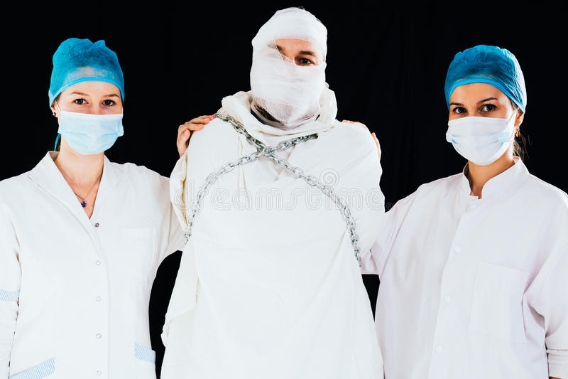 Hombre de la camisa de fuerza calmado abajo por las enfermeras fotografía de archivo