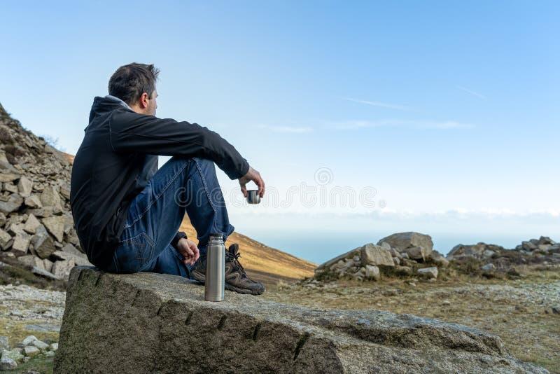 Hombre de la Edad Media que se sienta en la roca que bebe un té o un café por la mañana fría que mira en el valle y el mar de la  imagen de archivo