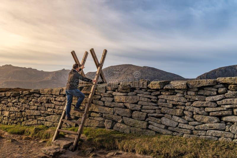 Hombre de la Edad Media que sube una escalera en la pared de piedra en las montañas, alcanzando hasta el futuro, puesta del sol e fotografía de archivo