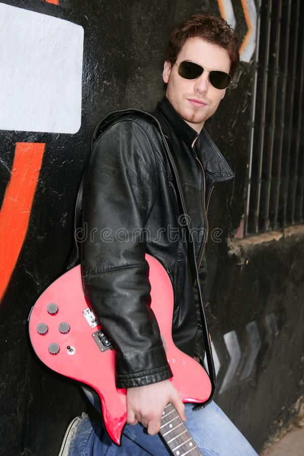 Hombre de la estrella del rock que sostiene la guitarra eléctrica fotos de archivo libres de regalías