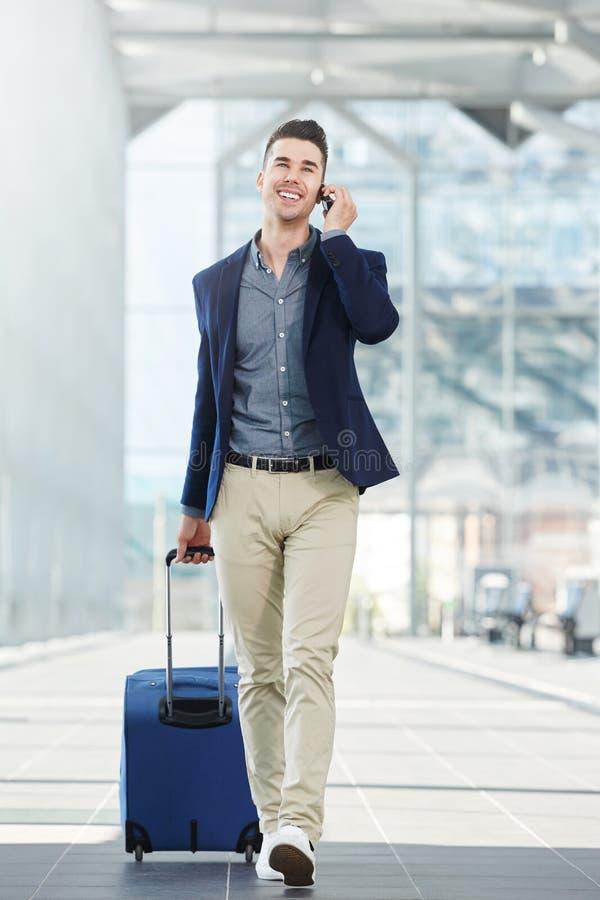Hombre de la indumentaria de oficina informal en llamada de teléfono en la estación con la maleta fotografía de archivo libre de regalías
