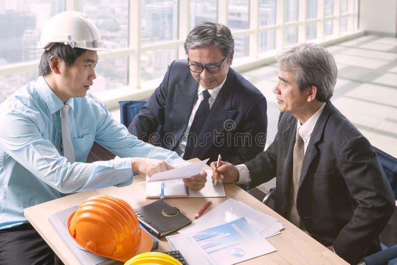 Hombre de la ingeniería y reunión mayor del proyecto de equipo de la arquitectura adentro imagen de archivo libre de regalías