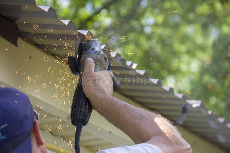 hombre de la mano del trabajador que sostiene la cuchilla quebrada de la amoladora Peligro de usar las herramientas eléctricas Pr imagen de archivo