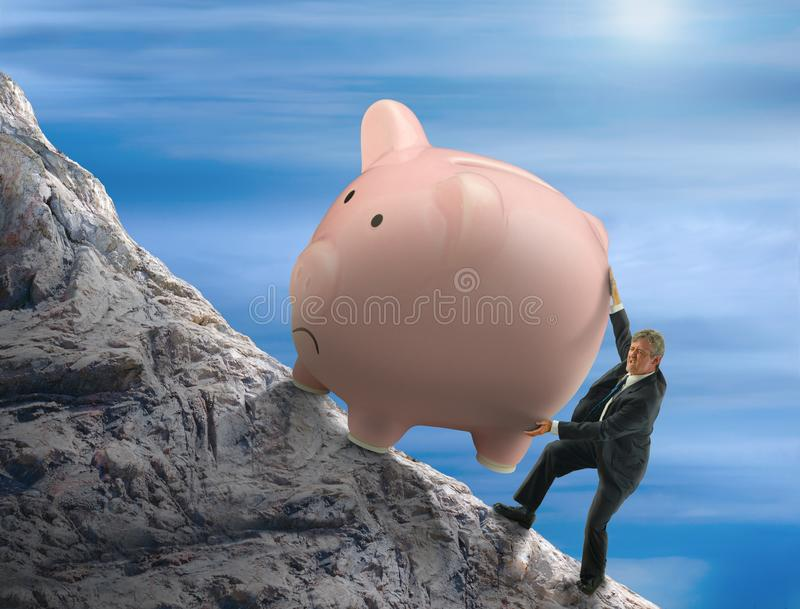 Hombre de la metáfora de Sisyphus que intenta empujar la hucha gigante encima de una montaña imagen de archivo libre de regalías