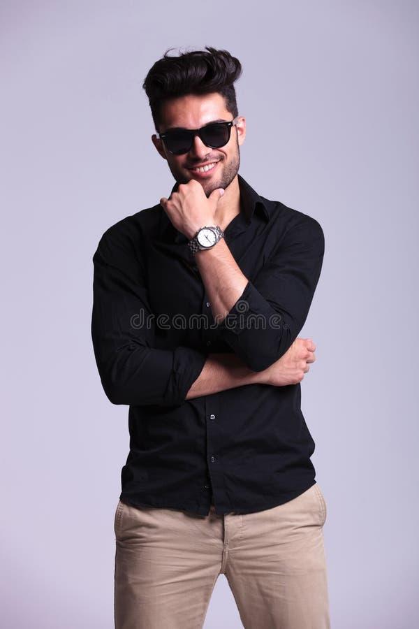 Hombre de la moda de los jóvenes con la mano en la barbilla foto de archivo