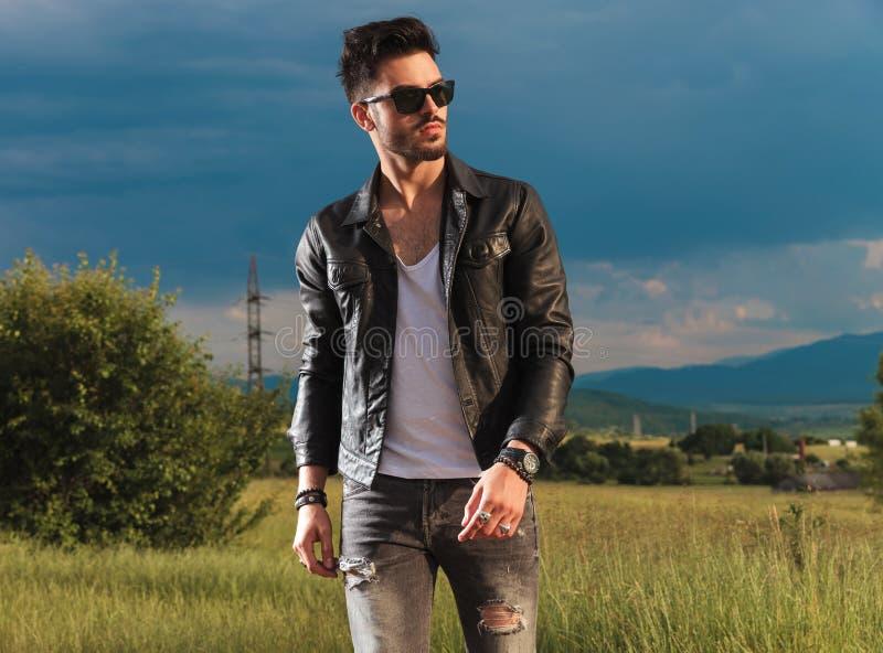 Hombre de la moda de los jóvenes en caminar de la chaqueta de cuero y de las gafas de sol imagen de archivo libre de regalías