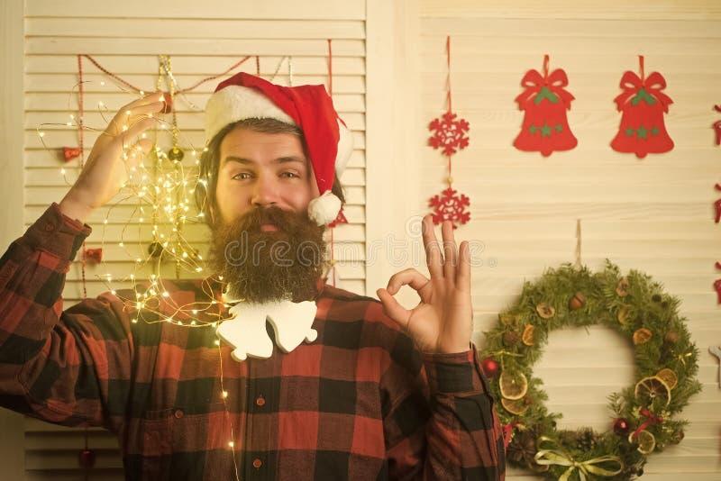 Hombre de la Navidad con la barba en cara y la guirnalda felices foto de archivo