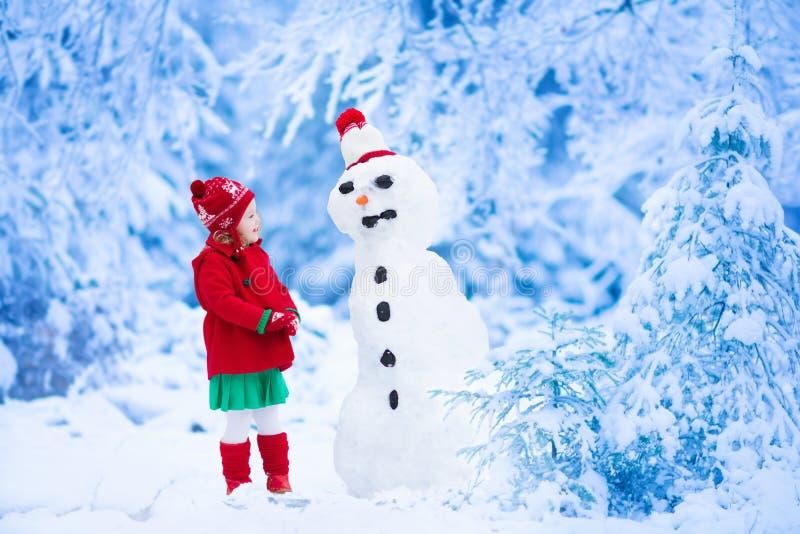 Hombre de la nieve del edificio de la niña en invierno fotografía de archivo libre de regalías