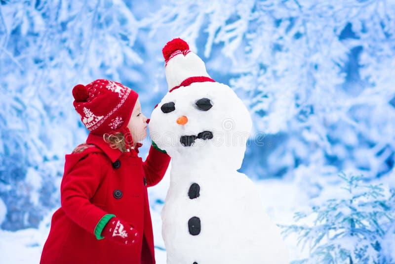 Hombre de la nieve del edificio de la niña en invierno imágenes de archivo libres de regalías