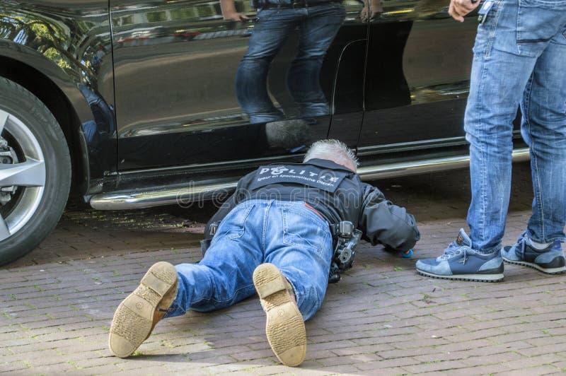 Hombre de la policía que comprueba los coches del Entourag de Obama Barack Leaving The Amstel Hotel en Amsterdam los Países Bajos foto de archivo libre de regalías