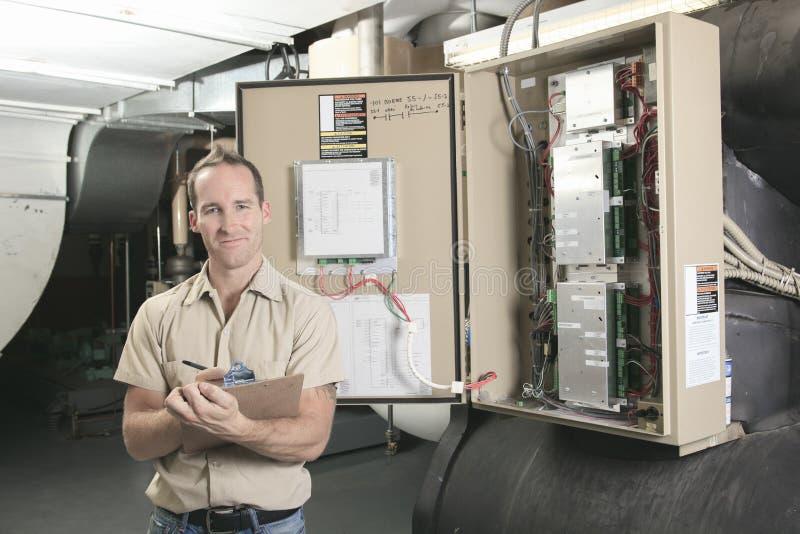 Hombre de la reparación del acondicionador de aire en el trabajo fotografía de archivo libre de regalías