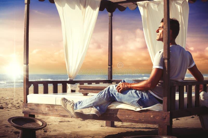 Hombre de la serenidad que se relaja en una cama del toldo en la playa de la puesta del sol imagen de archivo
