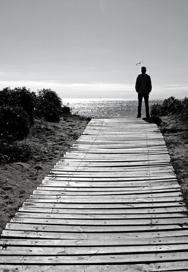 Hombre de la silueta en el camino de la playa fotos de archivo