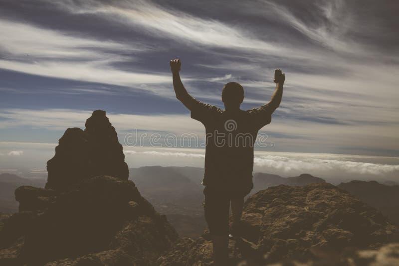 Hombre de la silueta que aumenta para arriba las manos en la montaña fotos de archivo libres de regalías