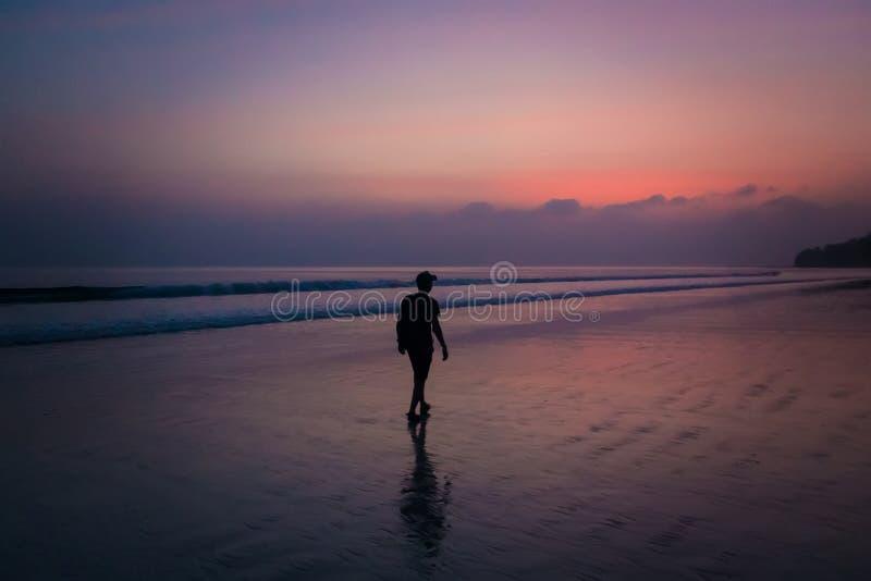 Hombre de la silueta que camina en la playa en la puesta del sol fotografía de archivo