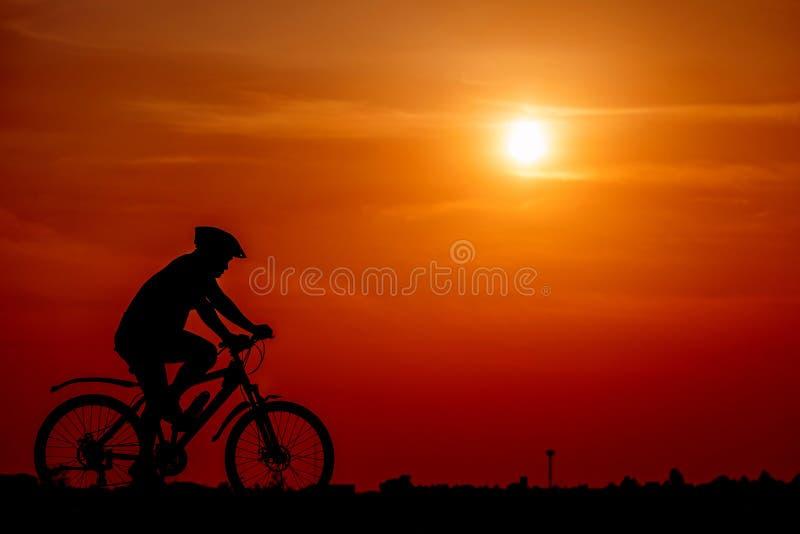 Hombre de la silueta que se sienta en la bicicleta en las texturas del fondo de la puesta del sol fotografía de archivo libre de regalías