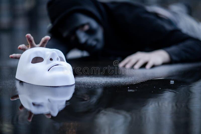 Hombre de la sudadera con capucha del misterio que intenta asir la máscara blanca imagen de archivo libre de regalías