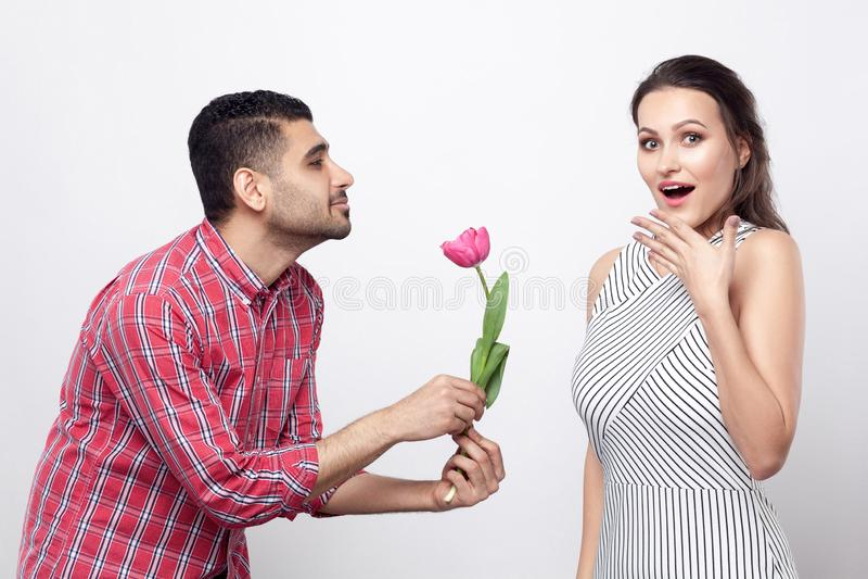 Hombre de la vista lateral que da el tulipán a la mujer emocionada Retrato del hombre hermoso en camisa a cuadros roja y la mujer foto de archivo