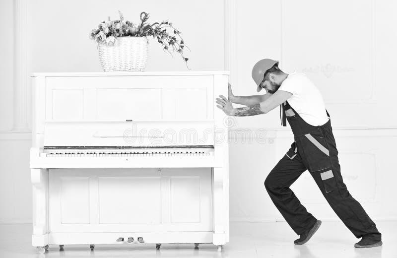Hombre de la vista lateral que intenta volver a poner el piano pesado aislado en el fondo blanco Músculos del edificio del hombre fotos de archivo libres de regalías