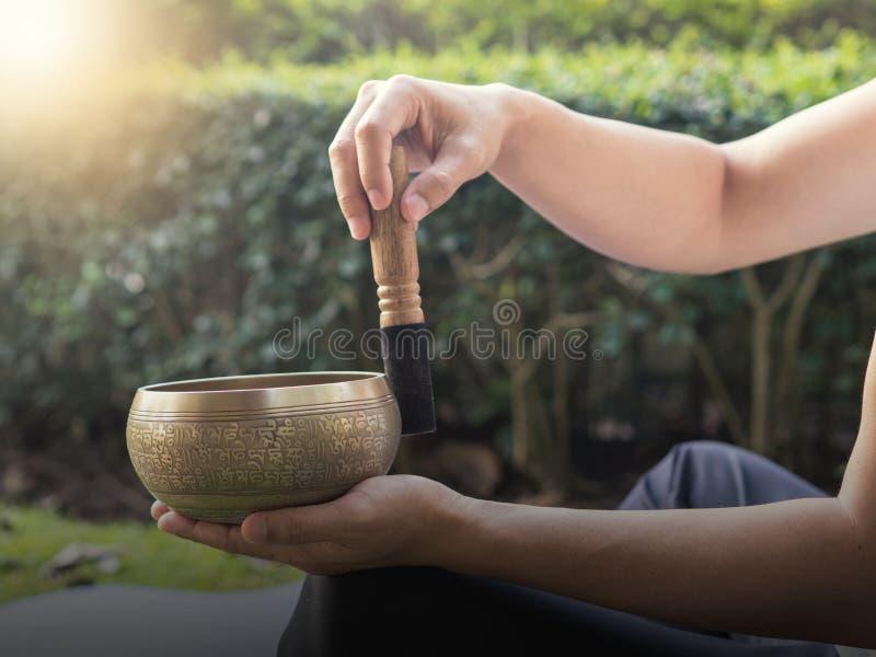 Hombre de la yoga con el cuenco del canto en el jardín foto de archivo libre de regalías
