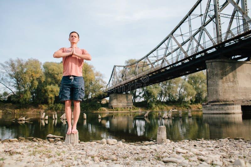 Hombre de la yoga que se coloca cerca del río en el tocón imagenes de archivo