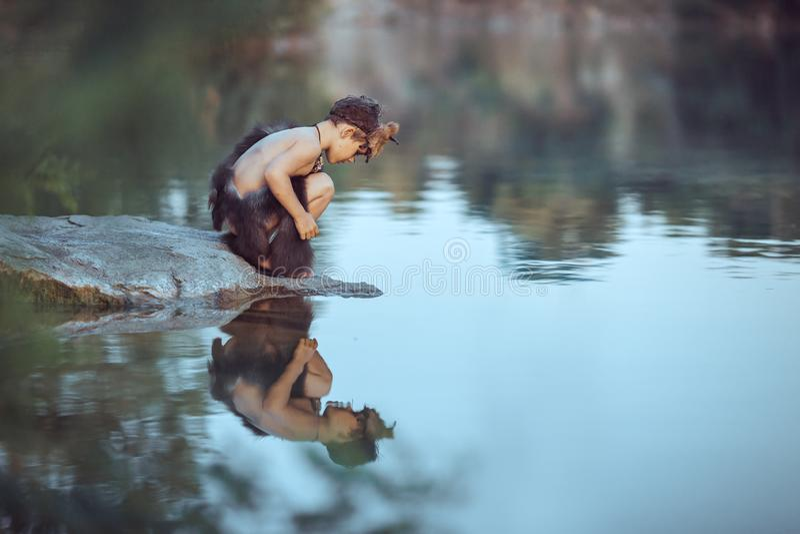 Hombre de las cavernas Niño pequeño que se sienta en la playa y las miradas en el agua imagen de archivo