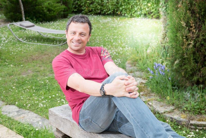 hombre de las vacaciones en casa feliz e individuo hermoso de la sonrisa en el jardín casero de la casa fotografía de archivo