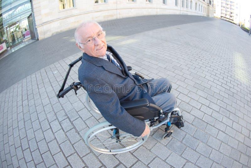 Hombre de los ancianos de la opini?n de Fisheye en silla de ruedas en el ambiente urbano imagenes de archivo