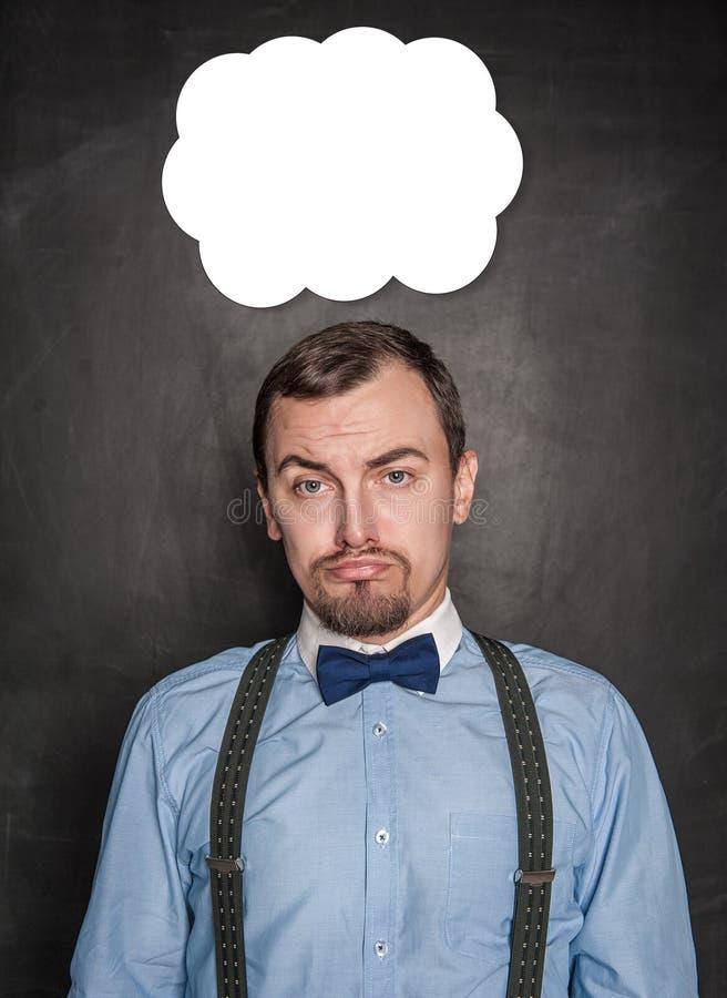 Hombre de los asuntos divertidos con la expresión triste en la pizarra imagen de archivo libre de regalías