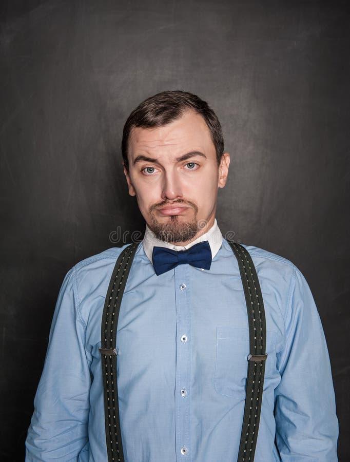 Hombre de los asuntos divertidos con la expresión triste en la pizarra imagen de archivo