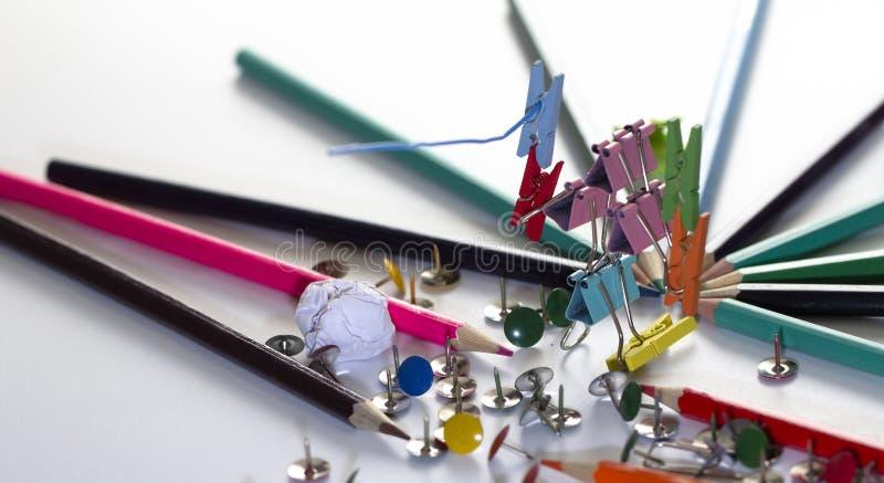 Hombre, de los clips multicolores de la oficina para el documento sobre foco selectivo del fondo blanco imagen de archivo libre de regalías