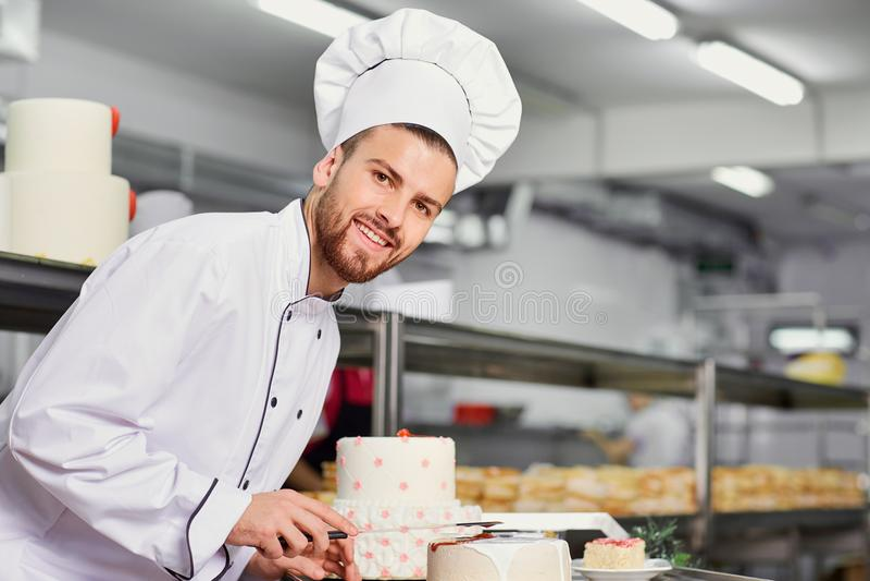 Hombre de los pasteles del cocinero que hace la torta en la cocina foto de archivo libre de regalías