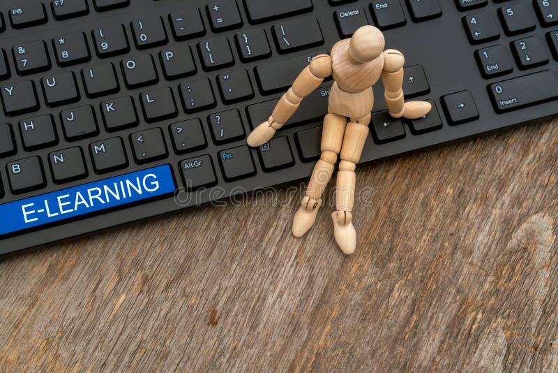Hombre de madera sentado en el teclado con el botón E-learning fotos de archivo libres de regalías